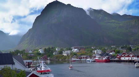 沿岸の : The pier with fishing boats and the yacht sails along the bay. Beautiful bay of a small fishing village Hamnoy. The Lofoten Islands. Norway 4k 動画素材