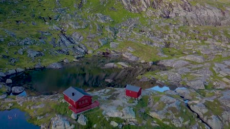 Скандинавия : Flying over small country house near a mountain lake. Beautiful scenery of northern Norway. Lofoten Islands. Munkebu 4k Стоковые видеозаписи