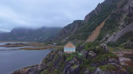 домик : Aerial view small country house on the promontory of the Norwegian Sea. Lofoten Islands. 4k