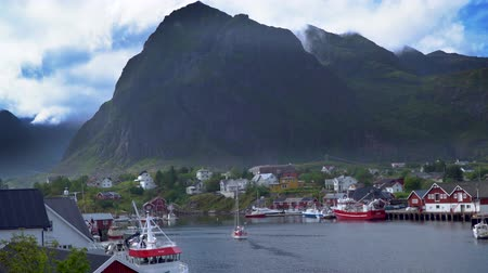 fishing village : The pier with fishing boats and the yacht sails along the bay. Beautiful bay of a small fishing village Hamnoy. The Lofoten Islands. Norway 4k Stock Footage