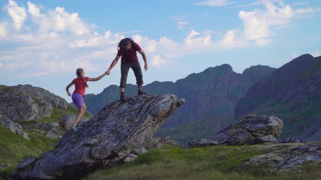 keşif : Father and daughter are traveling in the mountains. A man helps a girl to climb over a rock. Lofoten islands. Norway. Stok Video