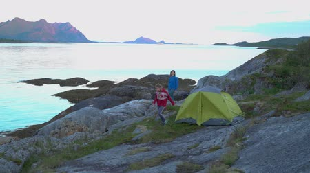 namiot : Mother and daughter near a tent on the shore of the Norwegian fjord. They embrace and are happy in their journey. Beautiful view of the mountains and the sea bay. Lofoten. Norway. 4K
