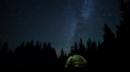 astro : The Milky Way is moving in the night sky over the silhouettes of trees and glowing tent. Timelapse. 4K