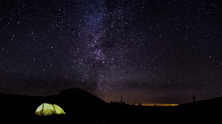 starlit : The Milky Way is moving in the night sky over the silhouettes of trees and glowing tent. Timelapse. 4K