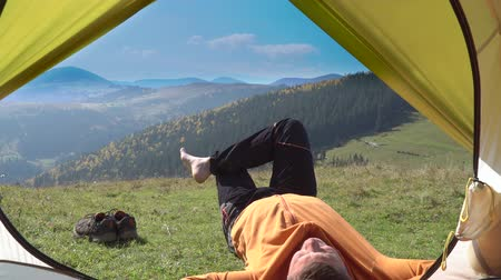 human foot : Camping man lying near the tent on the grass. From the tent view of the mountains. Hiking lifestyle during summer. Traveling alone in the mountains
