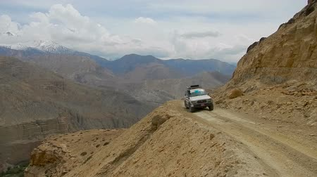 Тибет : The car goes on a very dangerous mountain road over precipices and a deep gorge. Extreme travel in the Himalayas. Such roads are in Nepal and the high-altitude Mustang. Стоковые видеозаписи