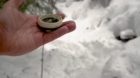 rehberlik : Close up on compass instrument in gloved hand . Mountain hiking trails. Winter mountain trip concept.