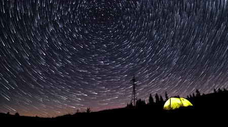 gece vakti : Time lapse of Star trails in the night sky over mountains and glowing tent. 4K Stok Video