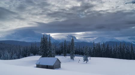 bulutluluk : Time lapse of flowing clouds over the mountains, forest and shepherds house covered with snow in winter. 4K