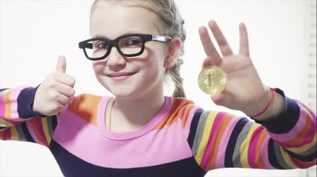 şifreleme : Young, cheerful, happy girl holding a golden billcoin in her hand and smiling at the camera over white background