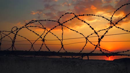 sürgün : Dramatic clouds behind barbed wire fence on a face wall