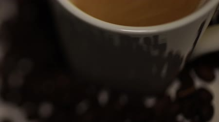 顔写真 : Blurred movie. Coffee from the coffee machine is poured into a white cup