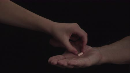 nanny holding : Close up. Hand of old man holding a pill on black background, Concept of illness and healthcare Stock Footage