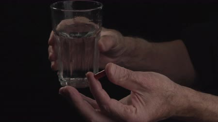 omega : Close up. Hand of old man holding a pill on black background, Concept of illness and healthcare Stock Footage