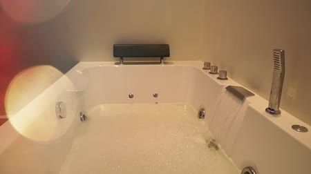 bagno di vapore : Water flows in jacuzzi. Spa bathroom with hydromassage and foam. Treatment beauty care Filmati Stock