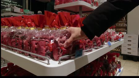 Girl chooses Christmas sweets in the supermarket.