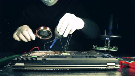 технический : Repairman solders the connectors to the computer circuit Board holding the soldering Iron and piece of tin in hands in the smoke from soldering. Close up