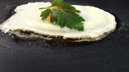 proteína : The egg is fried in a pan in melted butter. Fried eggs with parsley leaves