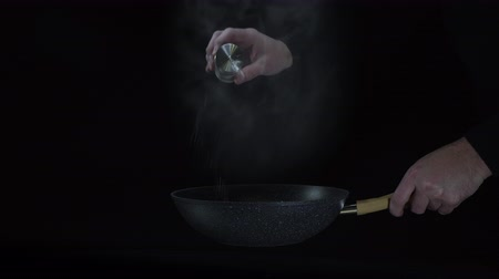 wok : Chefs hands seasons the hot dish with some salt. Stock Footage