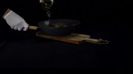 Chef adds olive oil to food in a pan. Slow motion