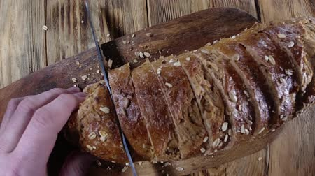 grzanki : Close up view. Man cuts bread into slices on wooden cutting board. Slices of bread Wideo