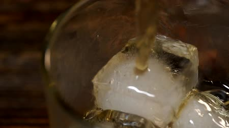 ice cube : Golden malt whiske poured into a glass glass with ice cubes Stock Footage