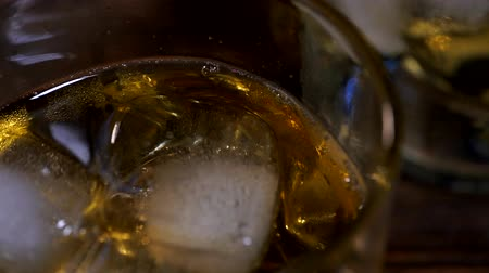 taje : Ice cubes fall into a glass with golden malt whiskey