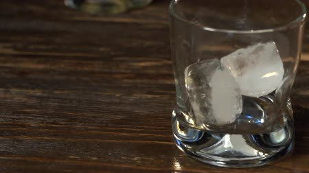 алкоголизм : Ice cubes fall into a glass with golden malt whiskey