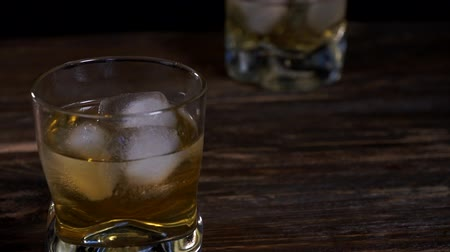 bourbon whisky : Ice cubes melts in a glass of malt whiskey. Stock mozgókép