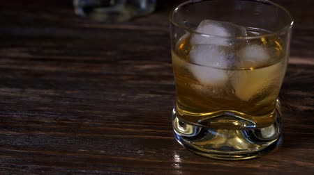pálinka : Ice cubes fall into a glass with golden malt whiskey