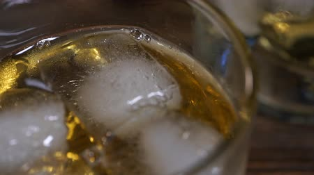 taje : Golden malt whiske poured into a glass glass with ice cubes Dostupné videozáznamy