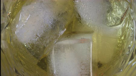 алкоголизм : Golden Whiskey with ice. Top VIew of ice cube falls and melts in a glass of whiskey.