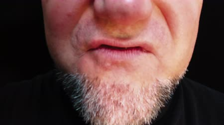 Closeup mouth of man with crooked teeth. Unshaven aggressive man swears.