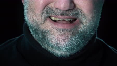 Angry man.Closeup mouth of man with crooked teeth. Unshaven aggressive man swears.