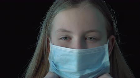 Portrait of a sick cute girl wearing a protective medical mask. Virus infection.