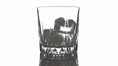 Golden Whiskey Pouring into Glass. Pouring of scotch whiskey or cognac into glasses with ice cubes