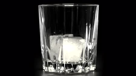 taje : Golden Whiskey Pouring into Glass. Pouring of scotch whiskey or cognac into glasses with ice cubes