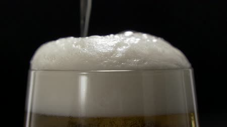 Fine bubbles rising In glass of beer on black background. Glass of beer close-up with froth in slow motion.