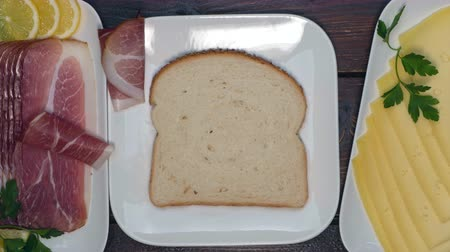 Making sandwich with ham, cheese and salad. Stop motion of preparing snacks