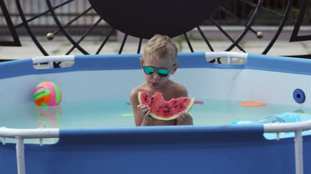 melão : Boy in black glasses eats watermelon in the pool