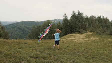 daleko : The boy runs and launches a snake in the mountains