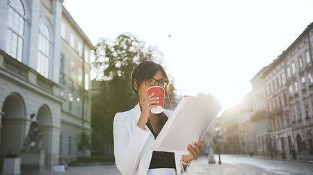 realization : A young business woman wearing glasses walking around the city and drinking coffee while looking at documents