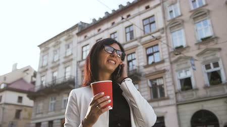 coffe : A young business woman walking around the city,talking on the phone and drinking coffee