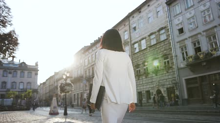 aktatáska : A young business woman walking around the city with a document folder