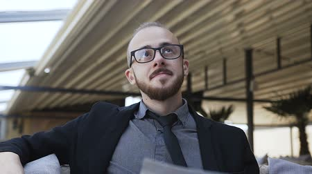 portföy : A young man with a beard in glasses is happy at work Stok Video