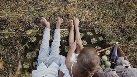 balya : Two young children sit in a field under bale of straw with bare feet. A boy with a girl eat fruit