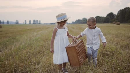 hat : A little boy helps a girl wear a straw suitcase in a white dress. Children walk in the field. Sunset