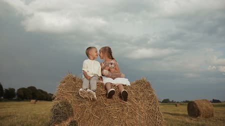 balya : boy with girl dressed in white clothes joyfully sitting in the hay after the rain and playing with toy bears