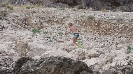 dalmácie : A beautiful boy walking on the beach of the Adriatic Sea and climbing high on the rock throwing sea stones in the water