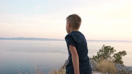şartlar : The boy stands on a cliff mountain and throws stones at the sea from the altitude. Sunset